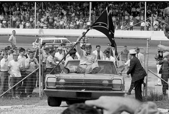 """Боб Ван Витценбург в образе Джонни Рэба едет на """"аллею победителей"""" на капоте машины Ричарда Петти"""